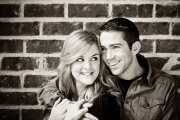 Smiling Couple Against Brick Wall